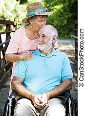 Senior Caretaker - Senior woman caring for her disabled...