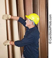 Senior Carpenter Arranging Planks In Workshop