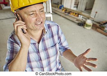 Senior carpenter having a call at workshop