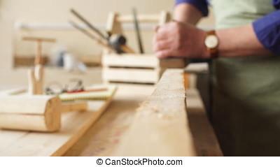 Senior carpenter is smoothing the edge of wooden planks.
