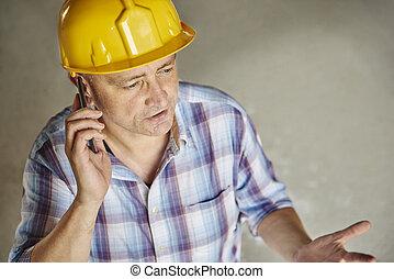Senior carpenter is using mobile phone