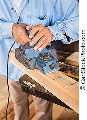 Senior Carpenter Shaving Wood With Electric Planer