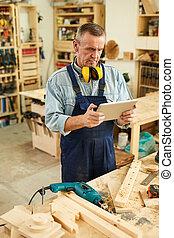 Senior Carpenter using Digital Tablet