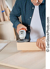 Senior Carpenter Using Electric Sander On Wood