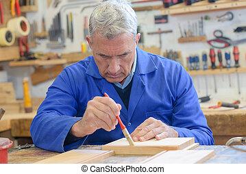 senior carpenter varnish wood at workshop