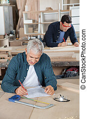 Senior Carpenter Working On Blueprint In Workshop