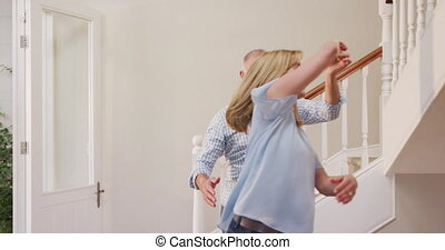 Senior Caucasian couple spending time at home together, dancing in the hallway, looking at each other and smiling, in slow motion.