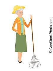 Senior caucasian farmer holding gardening rake.