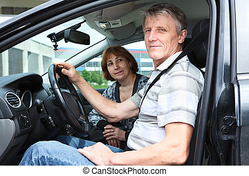 Senior Caucasian husband and wife sitting in land vehicle and smiling