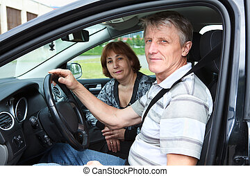 Senior Caucasian male and woman sitting in land vehicle and smiling