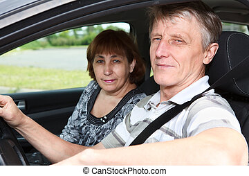 Senior Caucasian male and woman sitting in land vehicle together