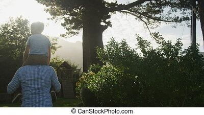 Senior Caucasian man and his grandson spending time in garden together on a sunny day, walking, the boy sitting on his grandfather shoulder, in slow motion.