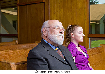 Senior Caucasian Man and Young Woman Sitting in Church Pew