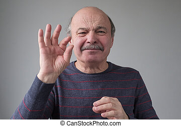 Senior caucasian man gesturing with hand showing small size sign with fingers