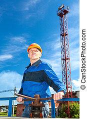 Senior Caucasian man in a working uniform with pipe valve. ...