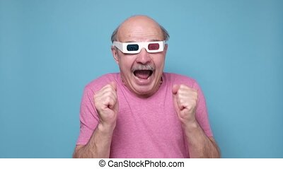 Senior caucasian man wearing 3D movie glasses watching interesting movie. Studio shot