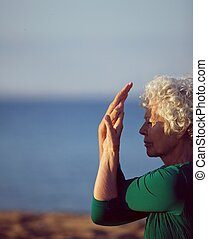 Senior caucasian woman exercising by the sea - Old woman...