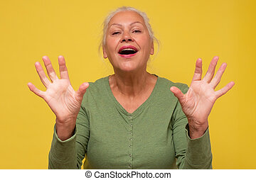 Senior caucasian woman is happy and shows ten fingers.