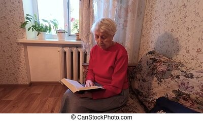 Senior caucasian woman reading a book at home