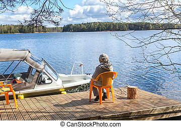 Senior Caucasian woman relaxing at the lake on pier