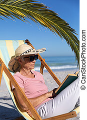 Senior Caucasian woman sitting on a deck chair and reading at the beach.