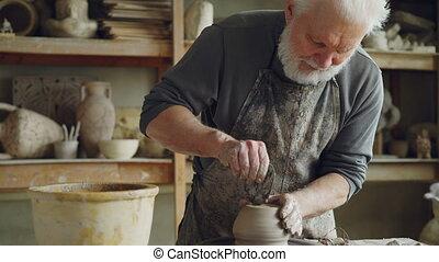 Senior ceramist is smoothing bottom of half-finished of...