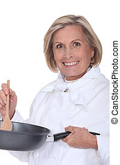 senior chef holding a pan