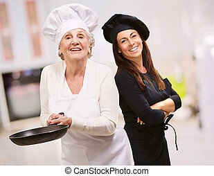 Senior Chef Holding Pan In Front Of Smiling Woman