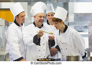 Senior chef showing food to his colleagues while being in...