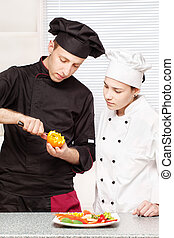 Senior chef teaches young chef to decorate fruit