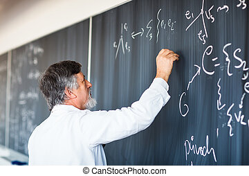 Senior chemistry professor writing on the board while having...