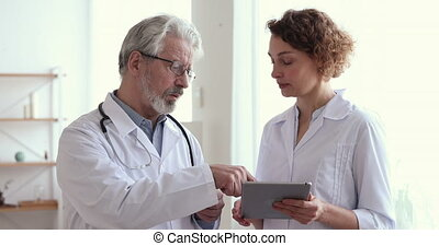 Senior chief physician helping young female doctor discussing patient diagnosis using digital tablet, handshaking. Happy younger doc shake hand thanking older medical worker for advice and teamwork.