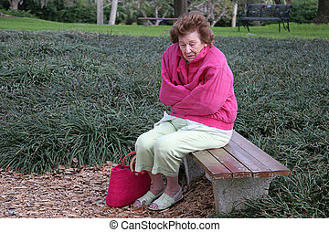 Senior Citizen Cold & Alone - A senior woman shivering in...