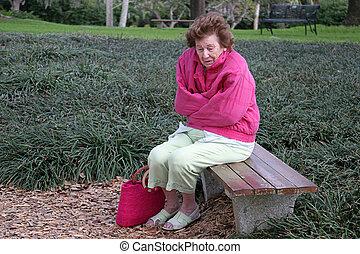 Senior Citizen Cold & Alone - A senior woman shivering in...
