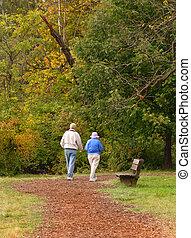 Senior citizen couple walking on path in autumn setting