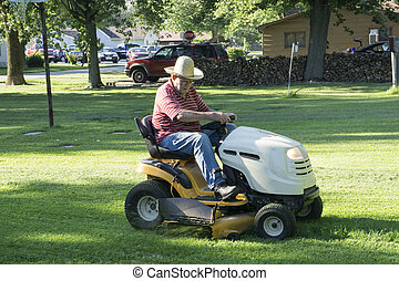 Senior Citizen Cutting Grass With A Straw Hat On