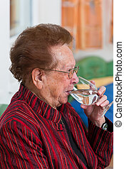 Senior citizen drinking water from a glass