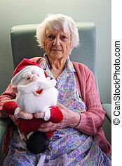 Senior citizen holding Xmas toy