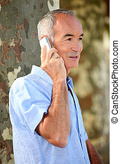 senior citizen making a call outdoors