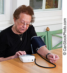 An old woman measuring her blood pressure