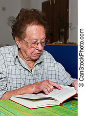 Senior citizen reads a book with glasses