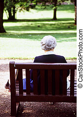 Senior citizen reading in a park.