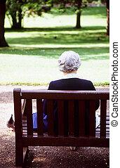 Senior Citizen - Senior citizen reading in a park.