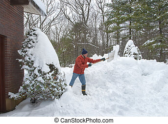 Senior citizen shoveling snow from his walkway after a big storm