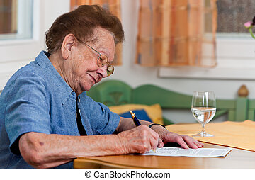 Senior citizen signs a contract - An old woman signs a...