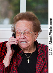 Senior citizen with a mobile phone call leads - Old woman...