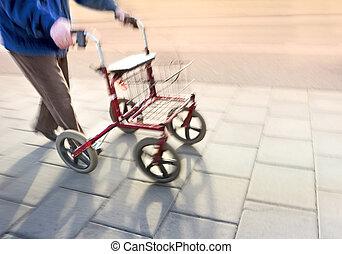 senior citizen with walking frame on sidewalk in blurred...