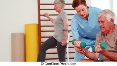 Senior citizens exercising with physiotherapist at the gym