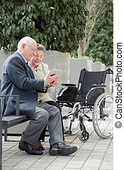 Senior citizens looking at tablet computer