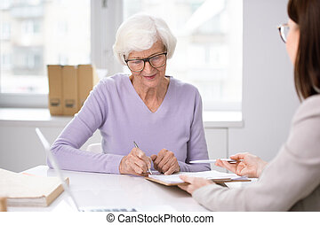 Senior client putting her signature in insurance agreement after consulting